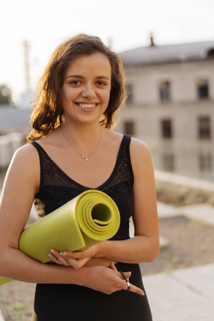 Smiling woman just finished yoga session holding yoga mat.