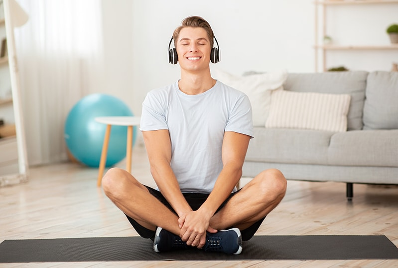 man enjoying music while practicing yoga